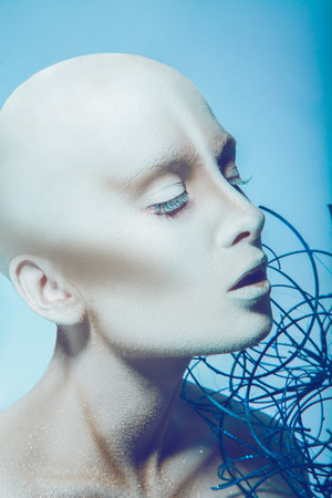 Bald woman with closed eyes in studio on blue background photo