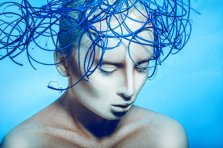 Cute woman with body art and closed eyes in studio on blue blackground photo