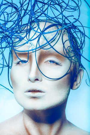 Voluptuous woman with creative decoration on head in studio on blue background photo