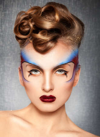 Gorgeous girl with creative multicolor make up in studio photo