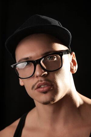 Fashion male in glasses looking at camera on black background photo