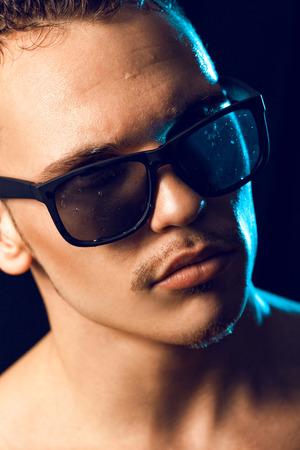 portrait of man in wet sunglasses in studio photo