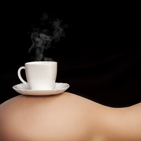 Cup of coffee on womans torso on black  photo