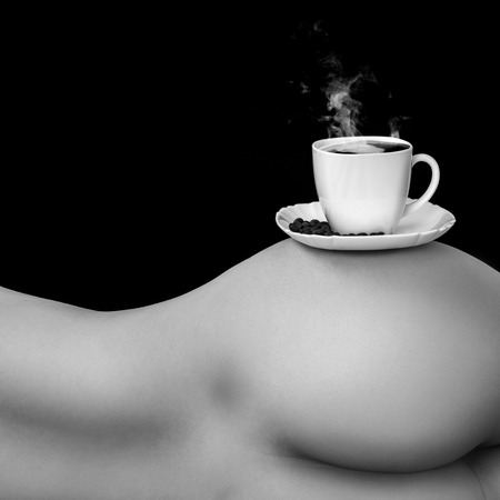 Black and white photo of coffee cup on torso in studio photo