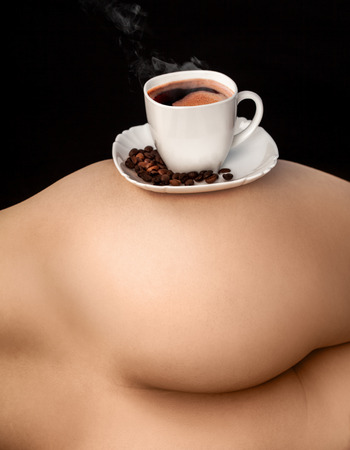 Cup of coffe on woman ass in studio photo
