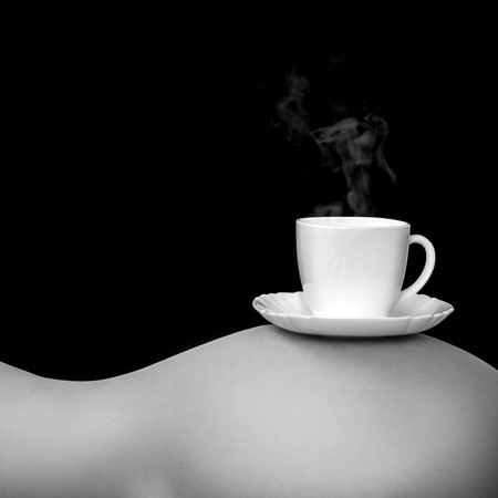 Gray tones photo of cup of coffee on womans torso on black  photo