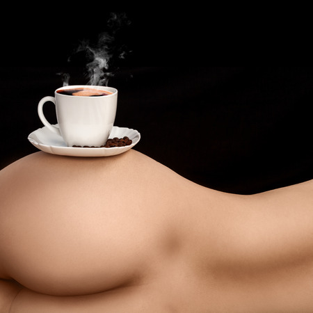 Square photo of coffee cup on womans torso in studio Stock Photo