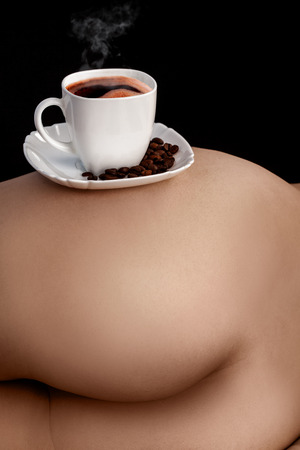 Vertical picture of coffee in cup on womans ass in studio photo
