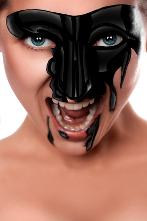Sexual female with black paint on face screaming in studio on white background photo