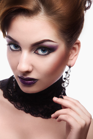 Cute female with violet make up looking at camera on white in studio photo