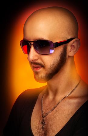Caucasian male in sunglasses looking away in studio on orange  photo