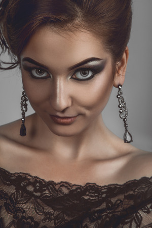 Luxury girl with sly look in grey in studio photo