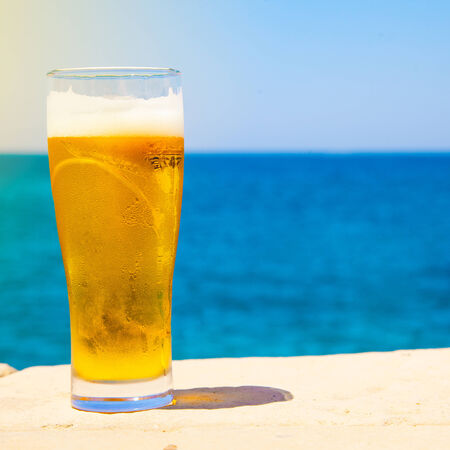 near beer: square photo of Glass of beer at summertime near sea Stock Photo