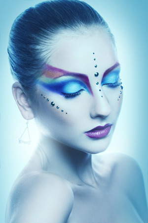 Attractive adult woman with multicolor makeup in cold tones studio photo