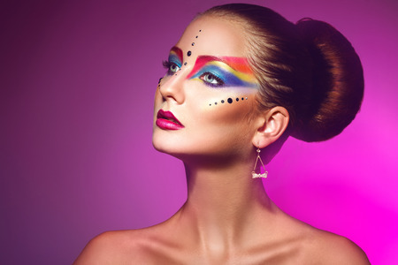 portrait of attractive woman with multicolor make up on purple background photo