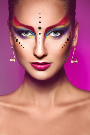 Portrait of fashion model with multicolor make up on purple background in studio photo