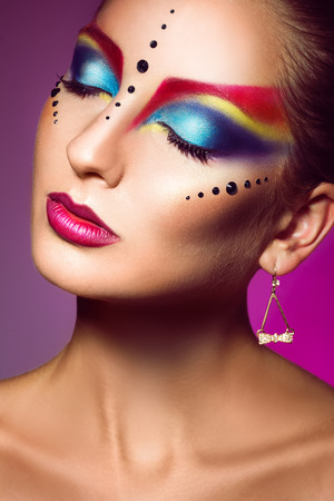 adult female with closed eyes and multicolor make up photo