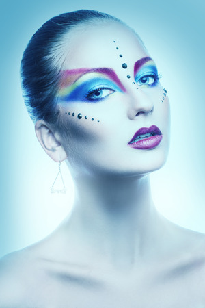 Sexy portrait of female with multicolor make up in cold tones in studio photo