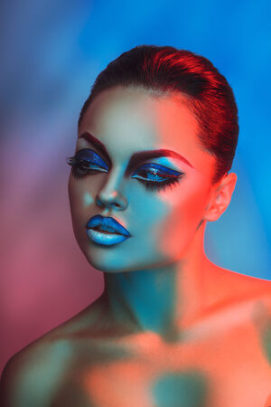 Fashion model in red and blue lights with healthy skin and makeup in studio photo