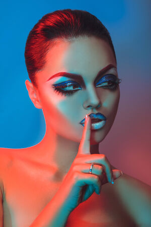Vertical photo of brunette with short hair and make up in red and blue lights in studio photo