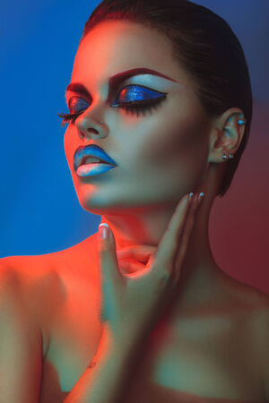 Sexy woman with make up and closed eyes in red and blue lights in studio photo