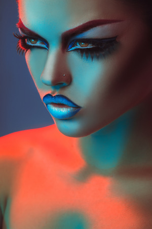 Portrait of beautiful adult woman in red and blue lights and make up in studio photo
