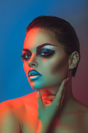Beauty woman with make up and healthy skin in red and blue lights in studio photo