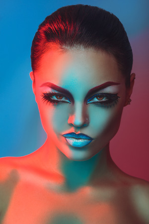 Glamour adult brunette with make up in red and blue lights in studio photo