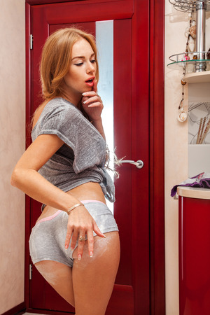 Gorgeous adult woman with flour hand print on bum in kitchen photo