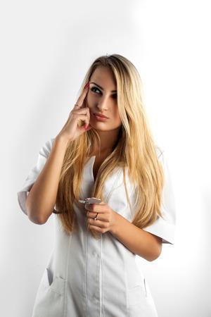 woman nurse thinking what pills to shoose in studio photo