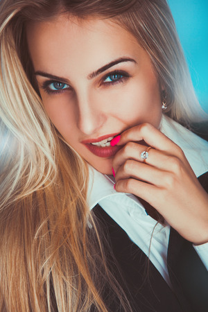 Seductive adult blonde woman looking at camera in studio photo