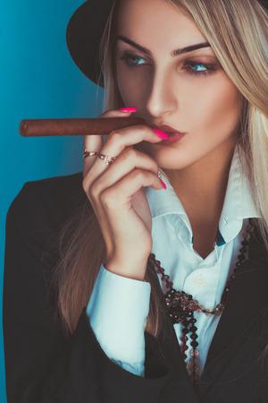 Gorgeous adult blonde woman smoking cigar in studio photo