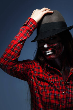 Studio photo of adult woman with scary make up for halloween on blue background photo