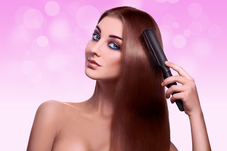 Portrait of charming sexy young adult woman with comb in studio on pink background photo