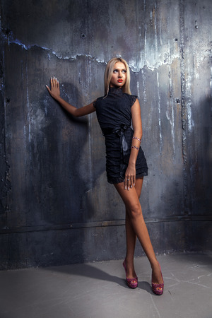 Full length photo of blonde woman in short dress looking away and standing near wall in studio photo