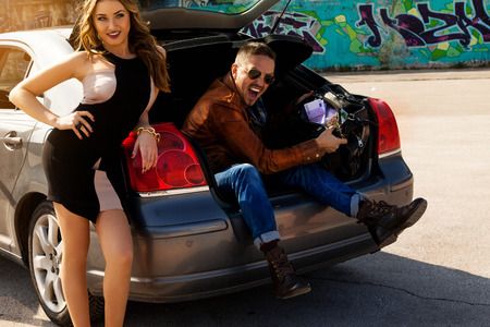 awesome couple enjoys bag full of money in trunk of car outdoors Stock Photo