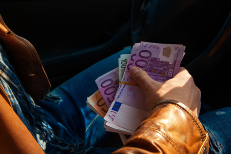 wads: close-up photo of male hand holding a wads of money. Inside car photo