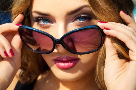gafas de sol: Retrato de joven hermosa atractiva con los ojos azules y gafas de sol al aire libre Foto de archivo