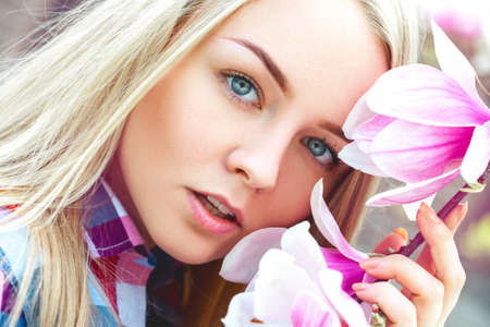 cutie: outdoors portrait of cutie young blonde woman with pink flowers. Spring time Stock Photo