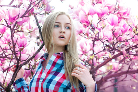 time sensitive: Sensitive beautiful girl near blossoming pink tree. Spring time