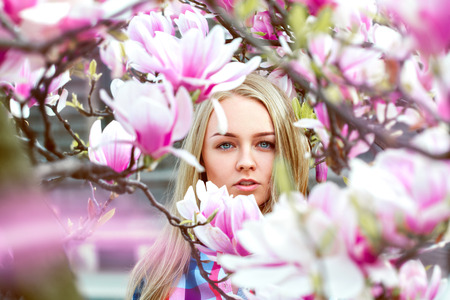 high society: High society blond lady in pink blooming flowers looking at camera outdoors Stock Photo