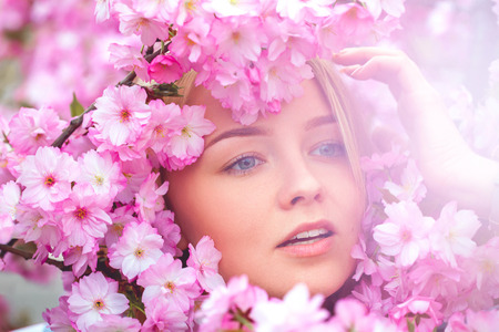 high society: spring outdoor portrait of a charming girl in flowers bloom. High society