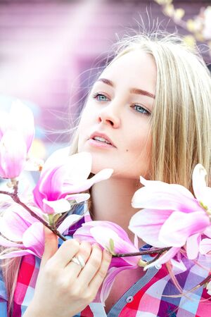Young charming lady dreaming in spring time with pink flowers on tree. Outdoors