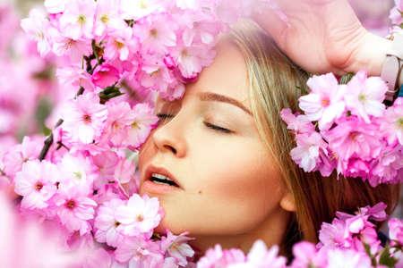 voluptuous: Voluptuosa mujer rubia joven disfrutar de las flores. Tiempo de primavera