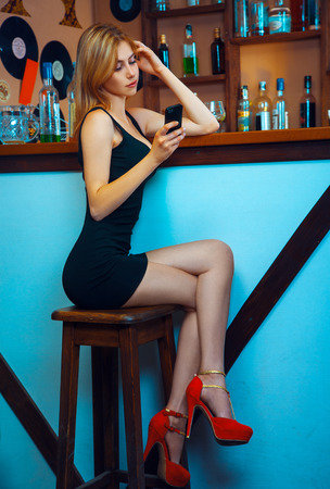 blonde woman in high heels and dress talking on a mobile phone in the bar. Vertical photo