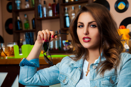 Close up portrait of sexy young adult woman with brown eyes and hairstyle in bar. looking at camera photo
