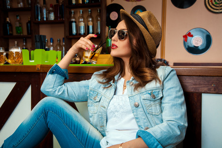 Elegant woman in sunglasses and hat drinking cold alcohol cocktail in bar and looking away photo