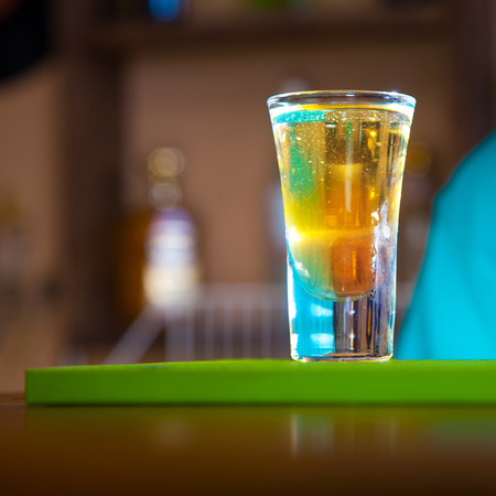 Square photo of short multicolor cocktail in bar. color image photo