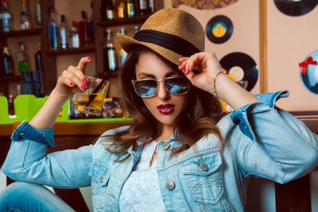 Young adult woman in sunglasses drink cocktail in bar. horizontal photo photo