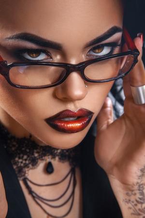 pretty teacher in glasses looking at camera in studio photo